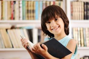 Niña sonriendo con un libro abierto.