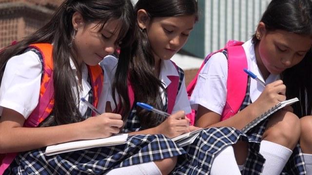 Estudiantes escribiendo en libretas