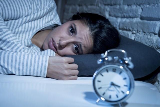 Un mujer acostada sin poder dormir.