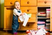 Niño pequeño haciendo travesuras con unas libretas.