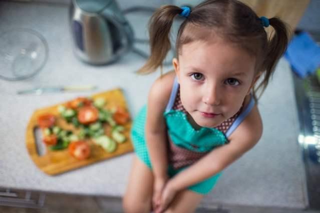 Una niña sentada con un plato de ensalada a su lado.
