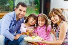 dos padres sentados con sus dos hijas sonriendo