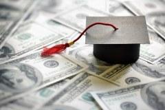 gorro de graduación encima de billetes.