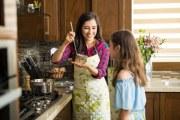 Madre enseñando a su hija a cocinar.