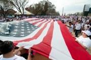 Varias personas sosteniendo una bandera estadounidense
