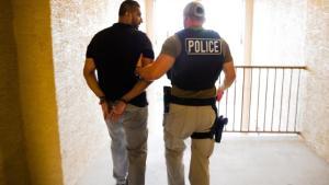 Oficial de ICE arrestando a un latino