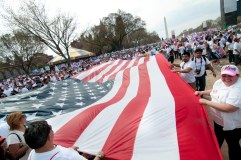 Varias personas sosteniendo una bandera estadounidense.