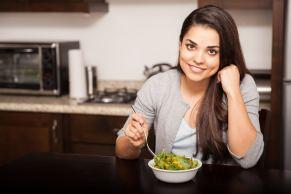 Una mujer comiendo una ensalada.