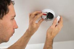 Un hombre cambiando la batería de la alarma del humo.