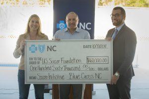 Representantes de Blue Cross NC presentando una donación para las mini canchas.