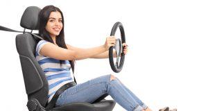 Mujer pretendiendo conducir sentado en un asiento de carro