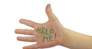 Un niño con su mano extendida y en ella escrita: ayuda