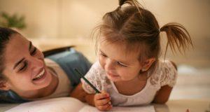 Una madre enseñando a su hija a dibujar.