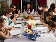 Familia setada en la mesa orando antes de comer