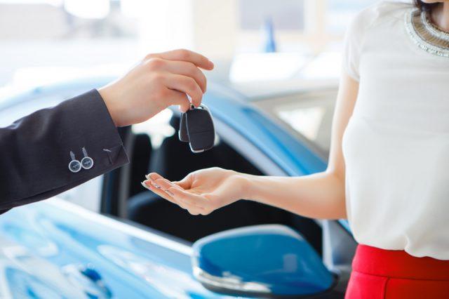 Una mujer recibiendo las llaves de su nuevo auto.