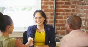 Tres adultos alrededor de un escritorio saludando con un apretón de mano