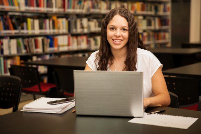 Estudiante joven sentada en frente de una portatil en la biblioteca
